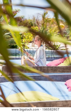 Fancy lady in white beach tunic reading book and relaxing by poolside of luxury spa resort set in lush tropical garden. Relaxation and wellbeing concept. Shot trough palm tree leaves.