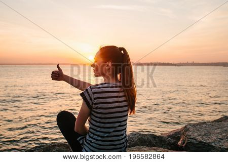 A young girl sits on the rocks next to the sea at sunset and shows a hand sign which means cool.