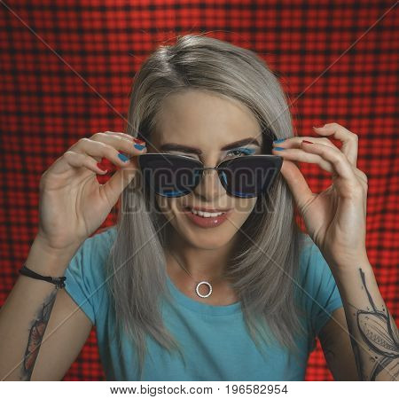 Portrait of a trendy hipster girl wearing glasses, winking at the camera, standing on a red checkered background. The concept of urban fashion. Turquoise shades. Portrait