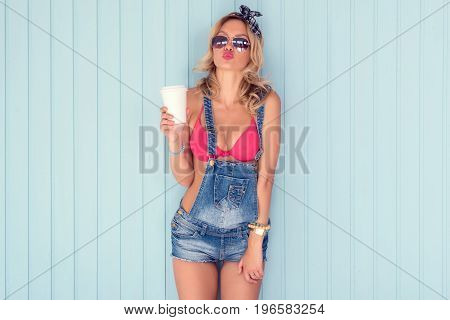 Beauty brunette woman portrait Beautiful girl looking and kissing at camera showing kiss lips holding cup of coffee take away.