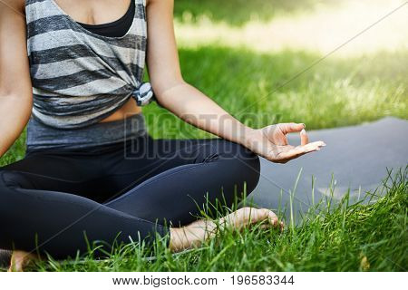 Close up of female hands sitting in lotus asana pursuing zen on a sunny summer day