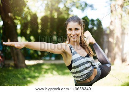 Girl practicing bikram yoga boses standing on one leg. Tuladandasana asana.