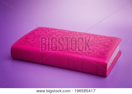 Closed Pink Bible On A Purple Background