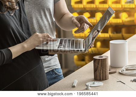 Couple is using a laptop in the workshop next to a table. On the table there are metal white and wooden cylindrical billets, cable, connector, key, bushings. Closeup. Horizontal.