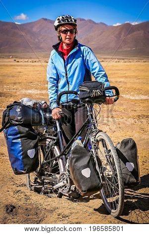 Female cyclist stuck in deep sand in the dry, desolate, empty rural countryside in central Bolivia