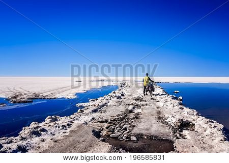 Lonely male cyclist travelling through the biggest salar in the world - Salar de Uyuni in Bolivia