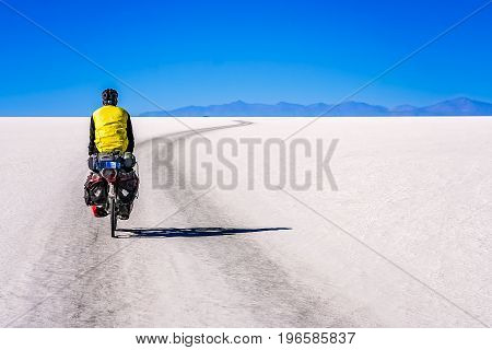 Lonely male cyclist travelling through the biggest salar in the world - Salar de Uyuni in Bolivia poster