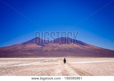 Lonely female cyclist travelling through the biggest salar in the world - Salar de Uyuni in Bolivia