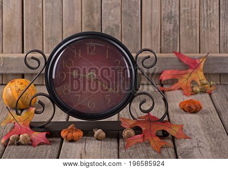 Clock with autumn decorations on a wood surface
