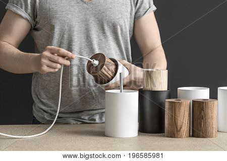 Worker holds a white lamp with a wooden part per the cable in the workshop. On the table there are other lamp billets. Indoors. Closeup. Horizontal.