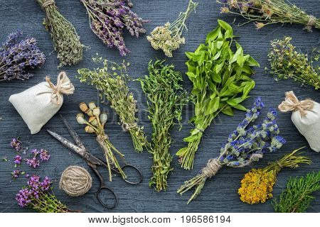 Medicinal Herbs Bunches, Sachet And Scissors On Wooden Table. Herbal Medicine. Top View, Flat Lay.