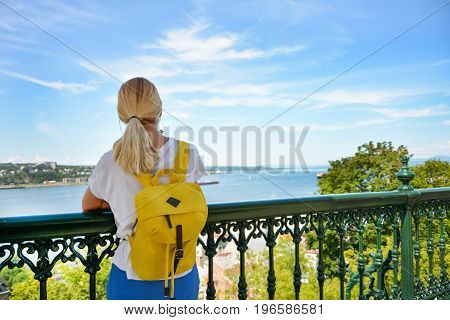 Blond girl with a backpack looking at the river Saint Lawrence at Quebec Canada Sanny day by Chateau Frontenac Castle