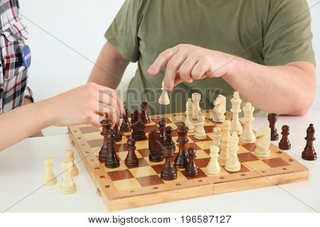 Young female volunteer playing chess with elderly man in light room