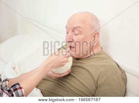 Young female volunteer feeding elderly man indoors