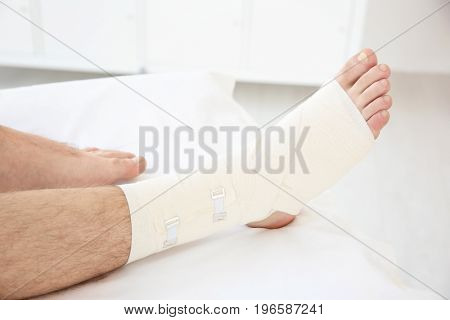 Young man with bandaged leg in clinic, closeup