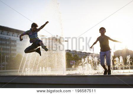kids jumping and having fun near a fountain