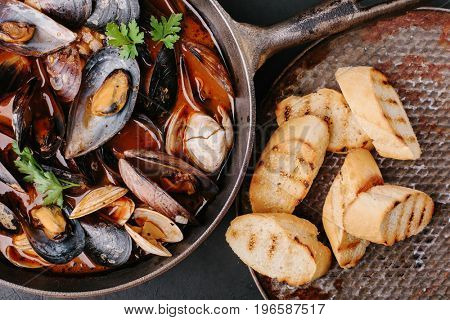 Mussels with sauce in a frying pan. French fries and croutons. close-up. view from above