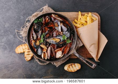 Mussels with sauce in a frying pan. French fries and croutons. view from above