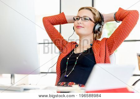 Young woman in office with headphones