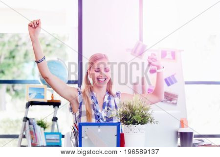 Young woman working in office cheering