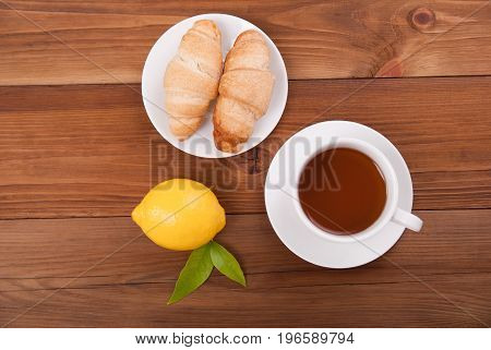 Cup of tea lemon and croissants on a wooden background. View from above .