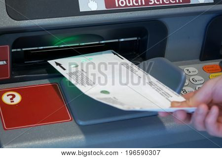 Woman inserting envelop to deposit money at bank