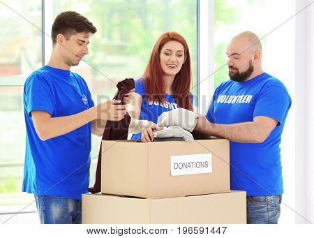 Young volunteers with boxes of donations indoors