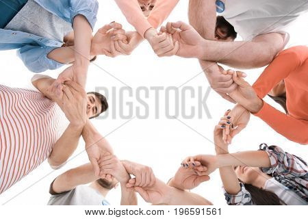 Group of young volunteers making circle with their hands on white background