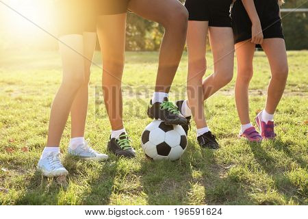 Children with ball on football field, closeup