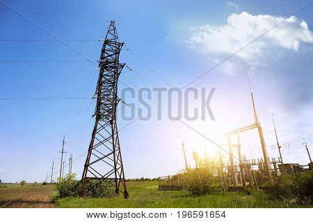 Field with electrical transmission tower and substation