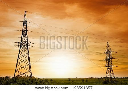 Field with electrical transmission towers at sunset