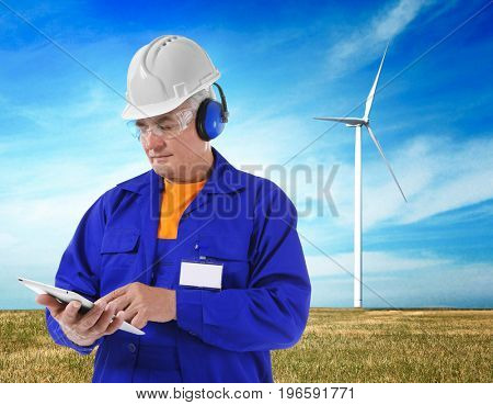 Senior engineer with tablet and wind turbine on background