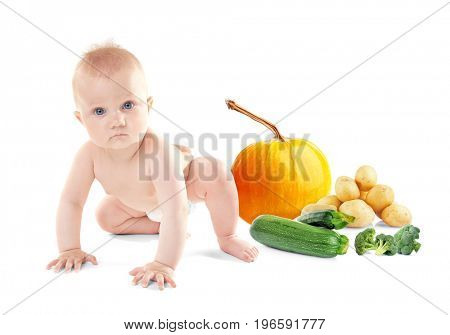 Cute baby with vegetables on white background. Healthy food concept