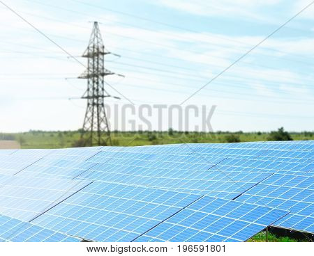 Solar panels and electrical transmission tower in field. Concept of eco friendly thechnology