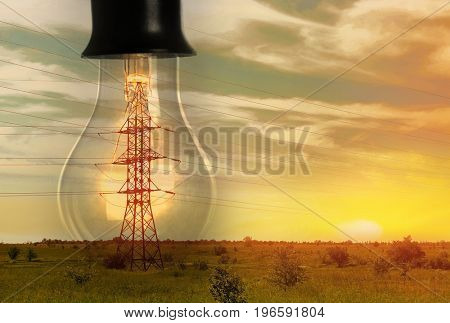 Field with electrical transmission tower inside huge light bulb at sunset
