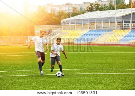 Boys playing football at stadium