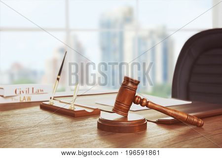 Judge's gavel on table in courtroom with cityscape view through window. Concept of law