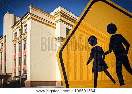 Children crossing sign and school building on background