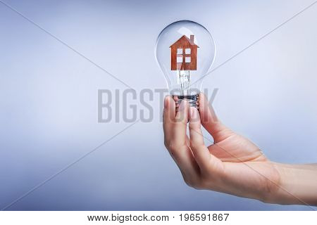 Woman holding light bulb with model of house inside on color background. Concept of energy consumption