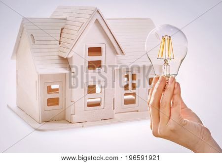 Woman holding light bulb and model of house on background. Concept of energy consumption