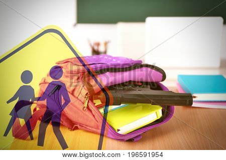 Children crossing sign and backpack with gun on table in classroom. School shooting concept