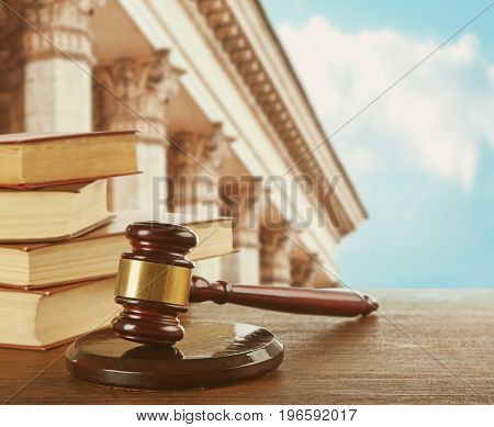 Judge's gavel with books and courthouse on background. Concept of law