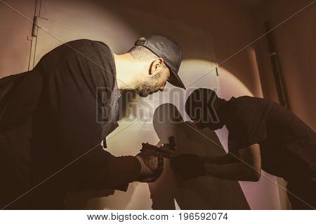 Terrorists opening classroom door at night. School shooting concept