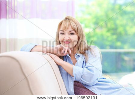 Attractive smiling mature woman sitting on sofa at home
