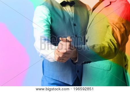 Gay couple dancing against color background on wedding. LGBT rights concept