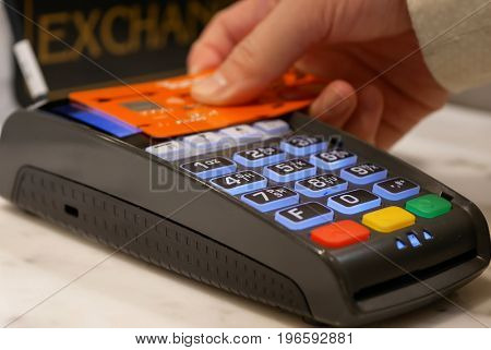 Coquitlam, BC, Canada - April 18, 2017: Woman tapping credit card on payment terminal for buying food
