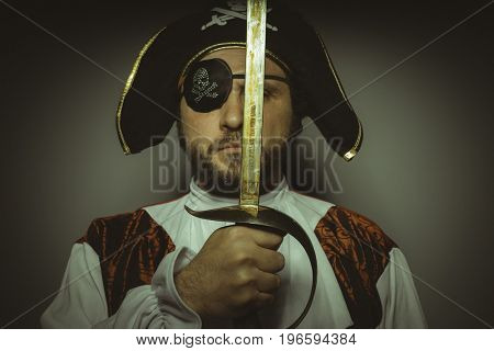 Man with beard dressed like a pirate, with eye patch and steel sword
