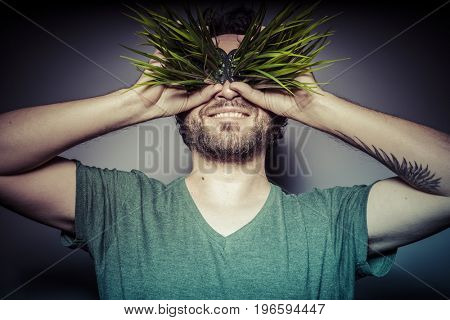 Cannabis, Concept of addiction to drugs, man with grass in eyes with gesture of happiness