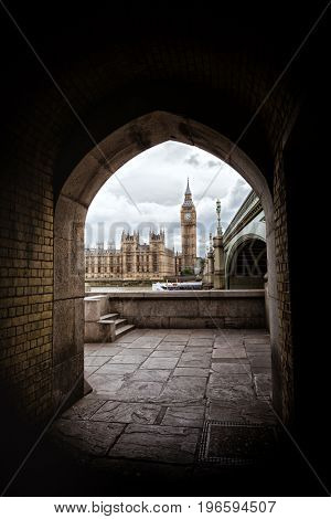 The Houses of Parliament, Big Ben and the Westminster Bridge, framed by a brick archway on the South Bank district of London.
