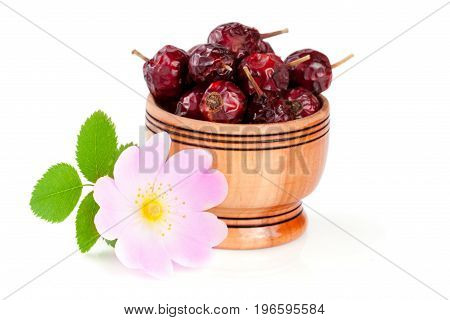 Rosehip flowers with leaf and rosehip berries in a wooden bowl isolated on white background.